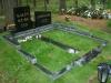 Graniidist hauapiire Tallinna Metsakalmistul, mitmekihiline, pealt poleeritud, servad murtud, muruvaip (00)