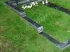 Graniidist hauapiire Tallinna Metsakalmistul, mitmekihiline, pealt poleeritud servad murtud, muruvaip