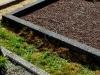 Hauapiire pesubetoonist, 4 hauakohta, must kild ja must tsement, laius-500cm, pikkus-250cm, serva laius-15cm, kõrge päis, sirge lilleriba, muld, graniitkillustik punakaspruun
